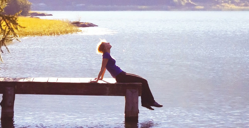 Woman sits in the sun on lake dock.