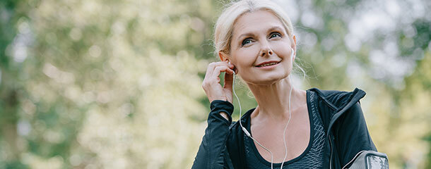 Recovering gut health patient listens to a podcast while exercising outdoors.