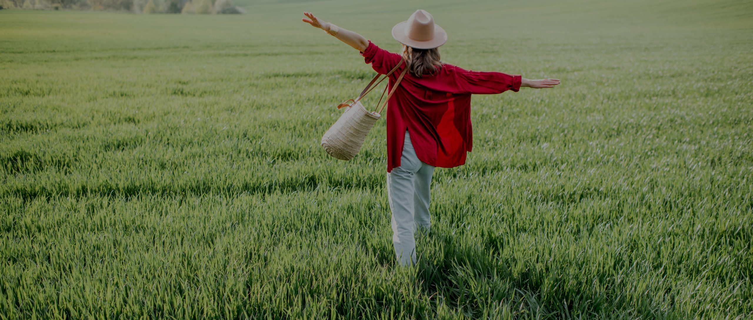 Woman in bright red shirt walks through field.