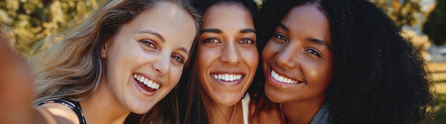 Three smiling women pose for selfie.